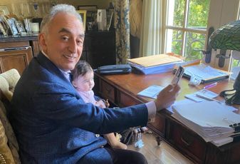 Universe Holdings Chairman and CEO Henry Manoucheri holds his grandson while working from home