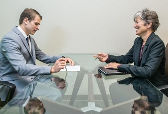 An interviewer and interviewee during a job interview in a sparsely decorated conference room.