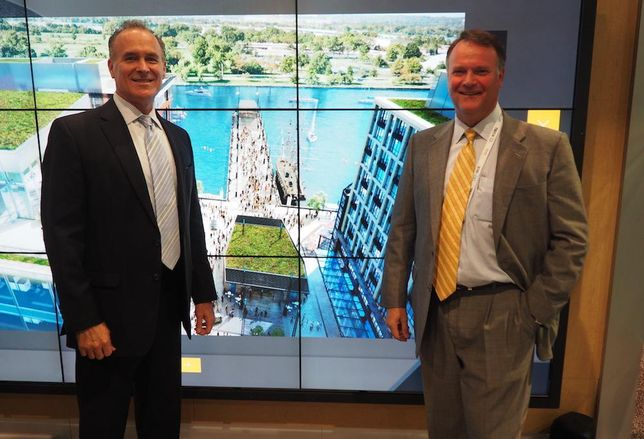 Ed de Avila and Peter Cole of Madison Marquette at ICSC RECon, in front of a rendering of The Wharf