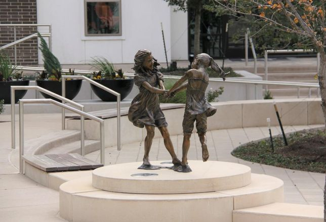 Angela Mia De La Vega's bronze and clay Whirlwind by Lot A Apartments depicts two young girls dancing. CityLine in Richardson