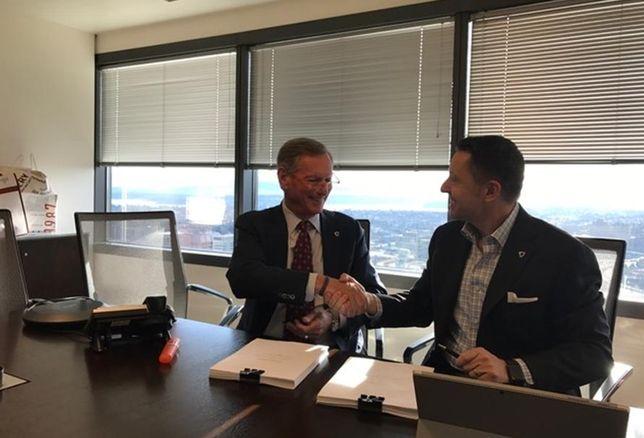Jeff Lyon and Robert Thornburgh, signing to merge Heger/Kidder Mathews