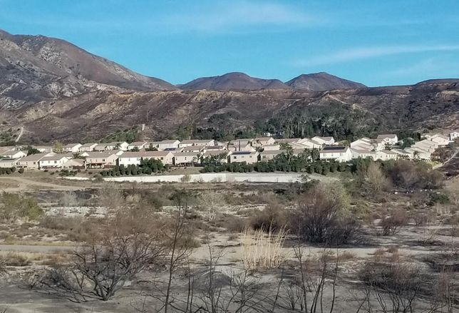 The photo shows how close the Creek Fire was to some neighborhoods in Sylmar. The Creek Fire has charred more than 15,000 acres and is 95% contained as of Monday. The wildfire has burned down 123 structures, nearly half were houses.