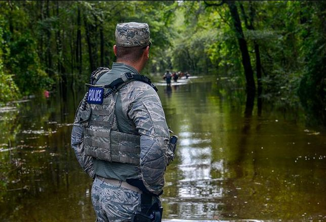 A U.S. Air Force Security Forces Airmen assigned to the South Carolina Air National Guard, 169th Fighter Wing, from McEntire Joint National Guard Base, working alongside Florence County, S.C., Sheriff's Department watches as citizens walk through a flooded road during evacuation efforts as the Black Creek river begins to crest in Florence, S.C., Sept. 17, 2018.