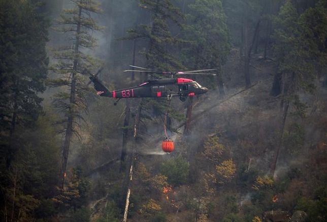National Guard members fly through Feather River Canyon to drop water on the Camp Fire.