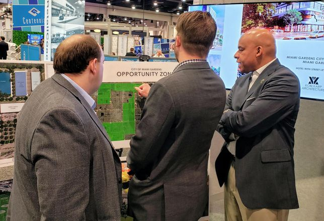 City of Miami Gardens Deputy City Manager Craig Clay talks to a couple of investors about the city's opportunity zone areas at ICSC RECon 2019.