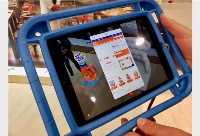 Thyng CEO Ed LaHood (not pictured) demonstrates environmental based augmented reality by holding up a smart tablet over the floor where a digital overlay of a Tide detergent product appears. When customers click on the digital product, it takes them to a website where they can order it.