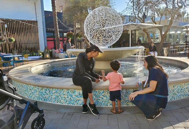 A young boy plays in front of an outdoor water fountain at the opening of CenterCal Properties' 2nd & PCH shopping center in Long Beach