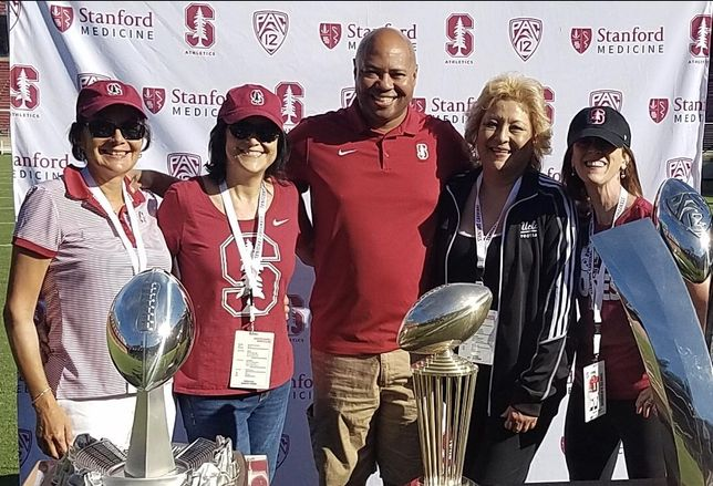 PGIM Real Estate Finance's Marcia Diaz (second from left) with her sisters and Stanford Football Head Coach David Shaw at a Stanford Women's Football Clinic.