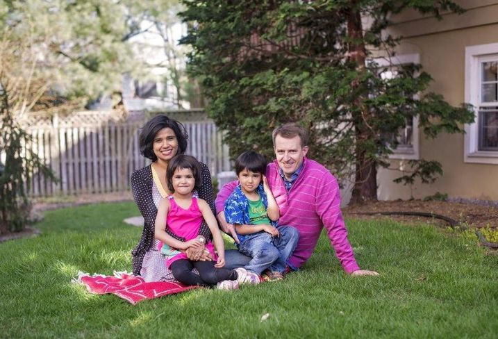 Revathi Greenwood sits with her family on their lawn at home.