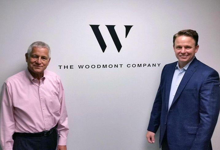 Stephen Coslik, chairman of the Woodmont Company, runs into his son, Erik, around the office.