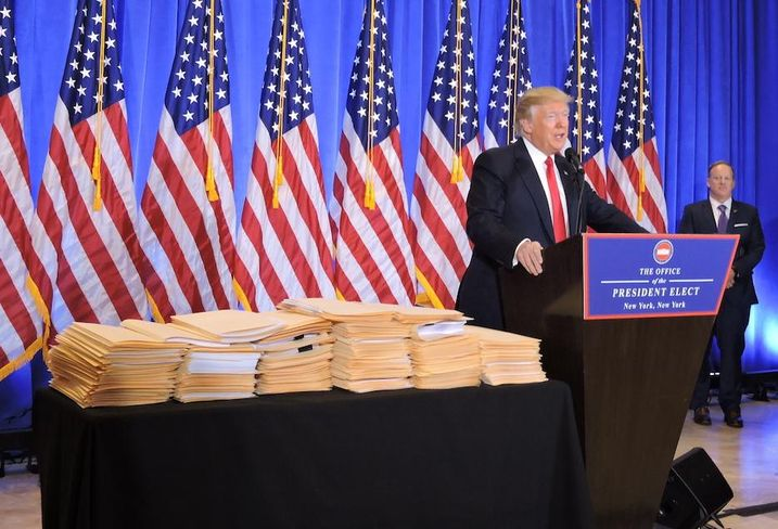 President-elect Donald Trump, next to the documents he says gives control of the Trump Organization to his sons at Trump Tower, Jan. 11, 2017.