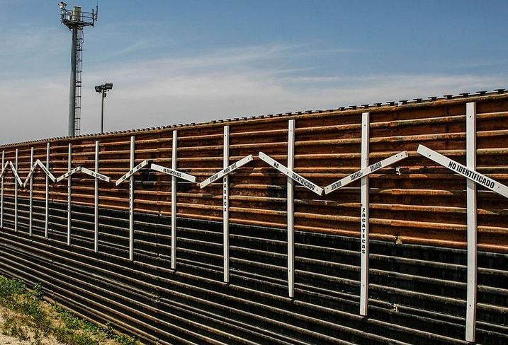 Mexico–United States barrier at the border between Tijuana and San Diego, with surveillance tower in the background.  The crosses represent migrants who died in the crossing attempt, some identified, some not.