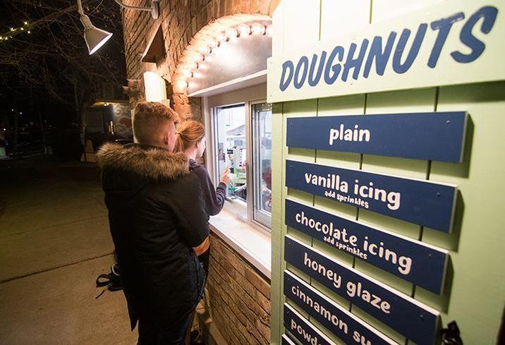 Customers order doughnuts via a walk-up window on the sidewalk at Reigning Doughnuts.