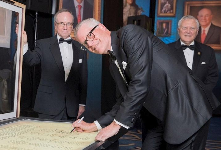 Delta CEO Ed Bastian adds his name to the Georgia Trustees as Georgia Historical Society President Todd Groce and Georgia Gov. Nathan Deal look on.