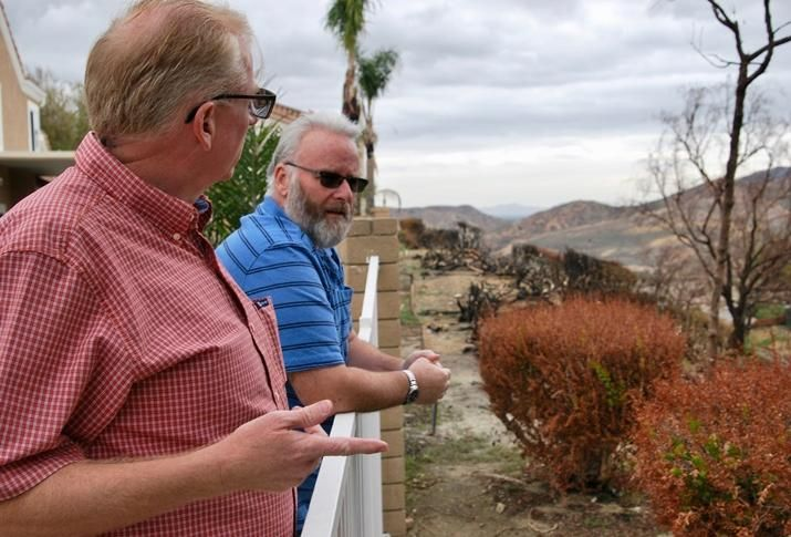 Brian Stanley and Willie Laundrie look at the charred vegetation that caught fire from the Canyon Fire 2 wildfire behind Laundrie's home in Anaheim Hills.