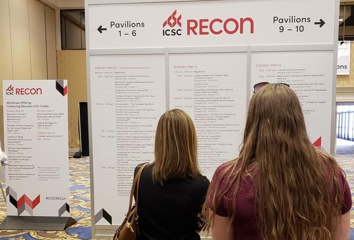 Attendees check out the schedule on day 1 of ICSC RECon