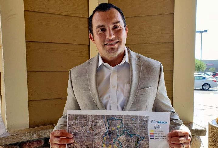 Long Beach Deputy Director of Economic Development Sergio Ramirez holds up a map of the opportunity zones in Long Beach.