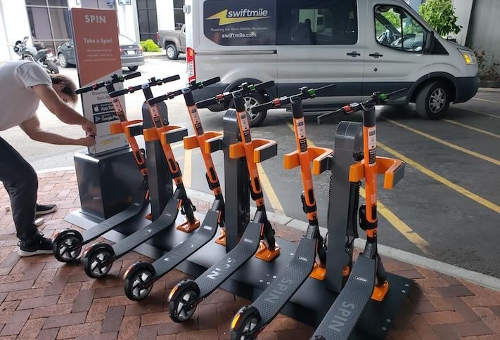 An electric scooter docking station with Spin scooters