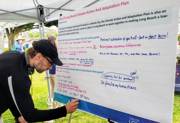 A resident writes down his suggestions on how the city of Long Beach can fight climate change during a climate fest event in Long Beach.