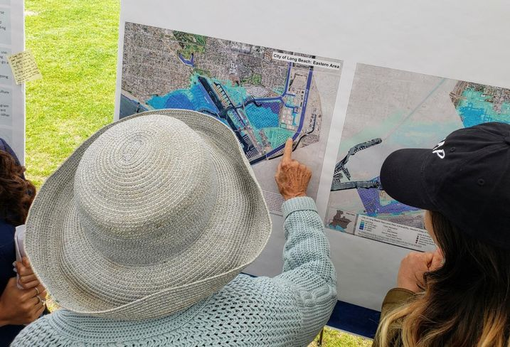 A woman points at an area in the Naples neighborhood of Long Beach that could possibly be affected by sea level rise due to climate change during a climate fest in Long Beach.