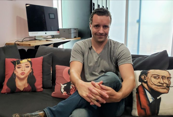 Upstart founder and CEO Jeremiah Adler sits down on a couch at one of his co-living buildings, the Hobart House, in Los Angeles