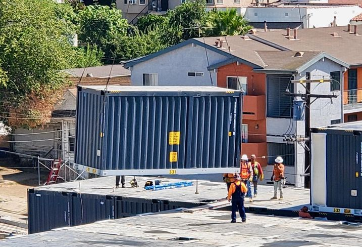 A crane lowers a modular unit on Hope on Alvarado, an 84-unit modular housing project for LA's chronically homeless, at 166 South Alvarado St. in Los Angeles.