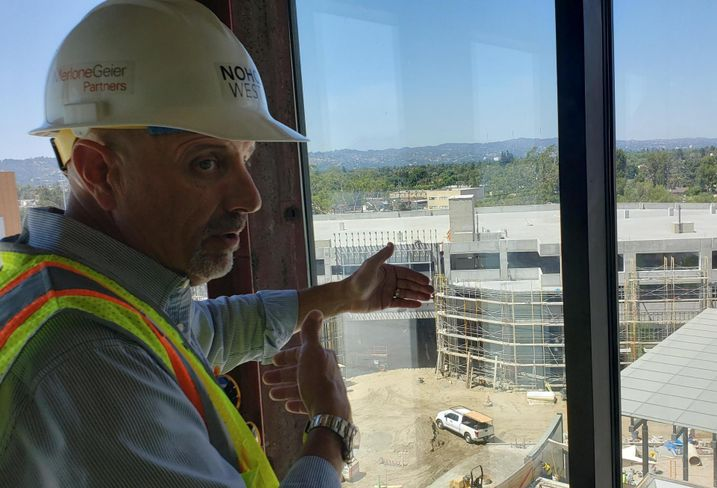 JLL's Patrick Church tours a Bisnow reporter at the construction of Merlone Geier's NoHo West project in North Hollywood