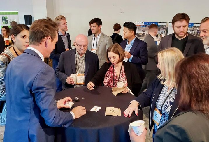 A magician entertains attendees at Bisnow's State of the Valley and Tri-Cities event at New York Life's 2300 West Empire Avenue building in Burbank