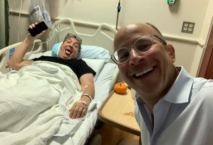 Metropolis Capital Advisors CEO Clifford Mendelson in a hospital bed after Game 7 of the World Series, along with Finmarc's Neil Markus