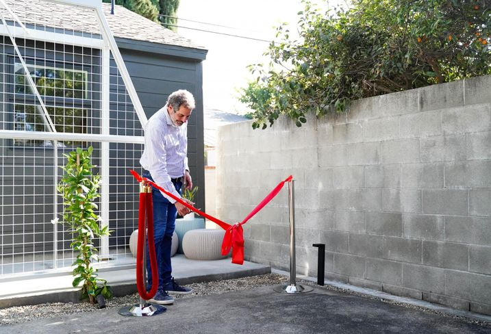 United Dwelling CEO Steven Dietz cuts the ceremonial ribbon at a resident's ADU in Los Angeles