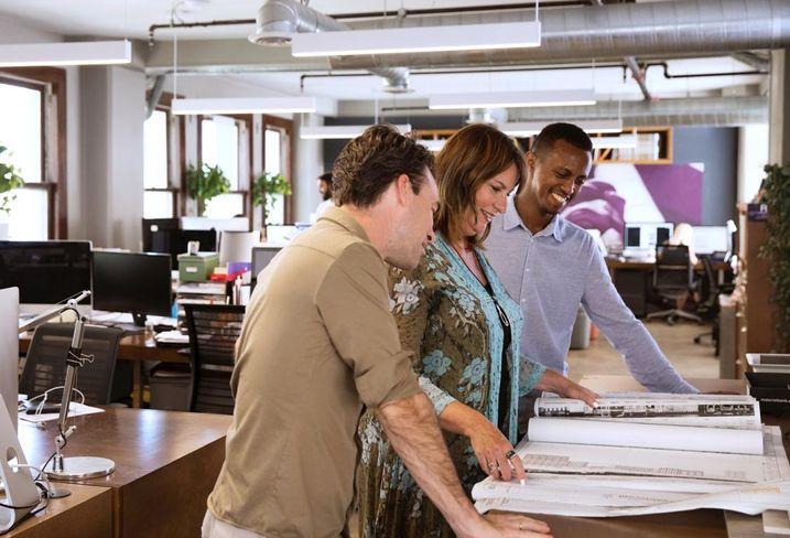 Omgivning Founder and Principal Karin Liljegren looks over design schematics with her team