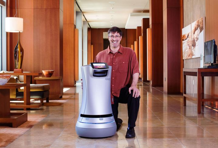 Savioke CEO founder and CEO Steve Cousins poses next to a Relay delivery robot