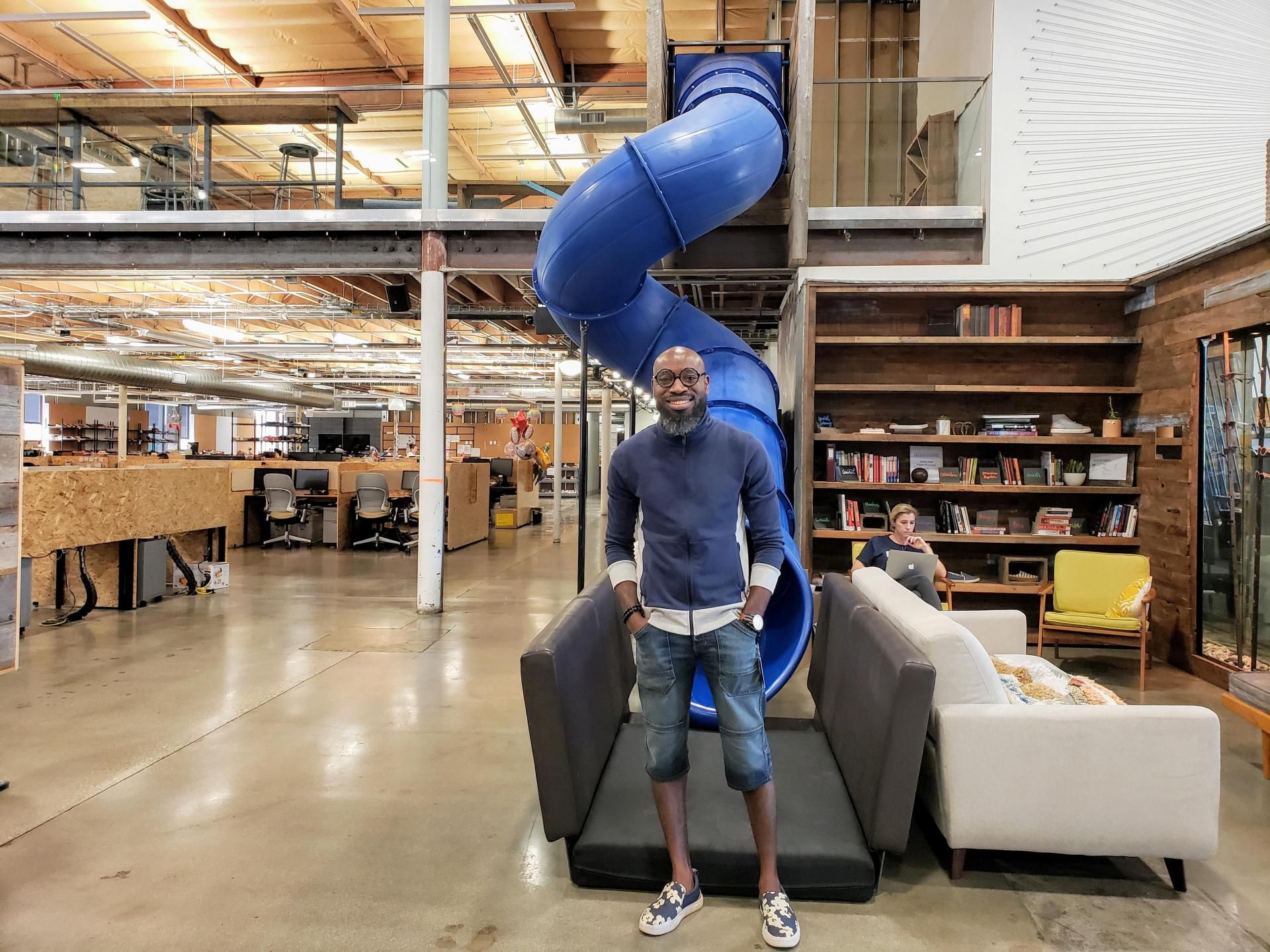 TOMS Facilities Coordinator Peter Efezokhae poses in front of a spiral slide inside TOMS' headquarters in Playa Vista.